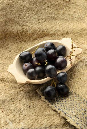 canva: Dark purple grapes on natural textured canva Stock Photo