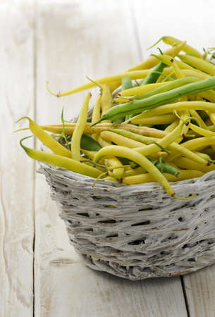 Yellow and green beans in basket on wooden background photo