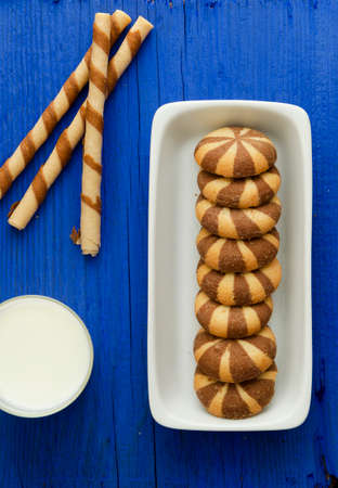 Striped chocolate wafer rolls and stake biscuits over blue background photo