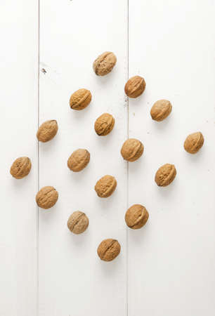 rhomb: Walnuts arranged in a symmetric rhomb shape over white table