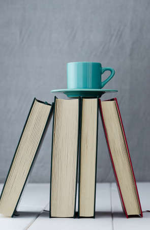 Blue coffee cup on top of four books photo