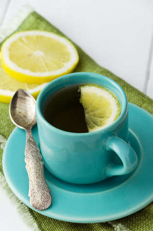 bluish: Close up of mint tea in blue cup with slice of lemon over green cloth