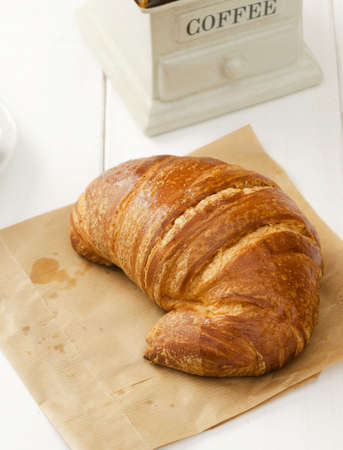Close up of croissant on brown paper over white table photo