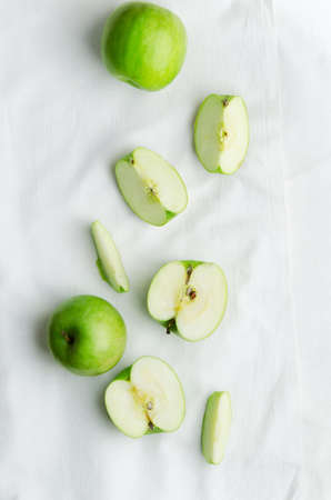 Green apples over white cloth, above view