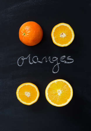 orange color: Orange fruits over black chalkboard with handwritten oranges word , above view