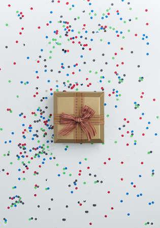 confetti: Gift box with confetti over white table