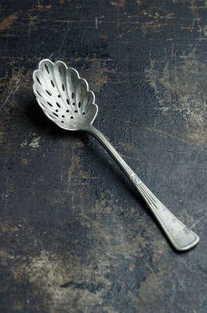 grunge silverware: Close up of a teaspoon over dark grunge background