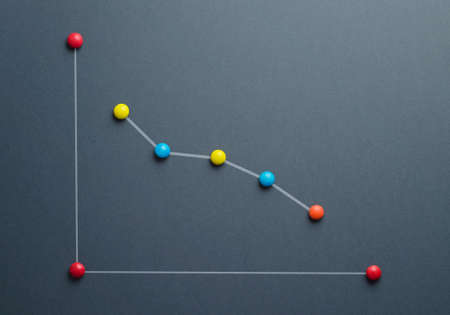 unsuccess: Decline graph concept made of colorful button shaped candies over dark blue background. This image is a photograph with a drawing over it. Stock Photo