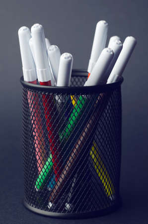 pencil box: Colorful markers in a pencil box holder over dark background
