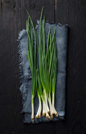 Spring onions over black wooden table, above view