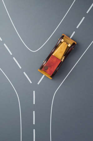 the right path: Transportation concept: Vintage wooden toy car on a doodle road over dark grey background, high angle view. Car goes to right and choose the right path. Stock Photo