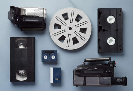 rollo pelicula: Cámaras de video VHS y Mini casetes y un rollo de película bien dispuestas sobre fondo azul, superior ver Foto de archivo