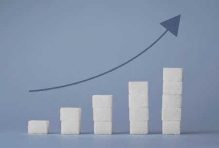 white sugar: Concept: Ascending stacks of sugar cubes and increase arrow over blue background. This in a concept for high risk of diabetes or other diseases caused by excessive consumption of sugar