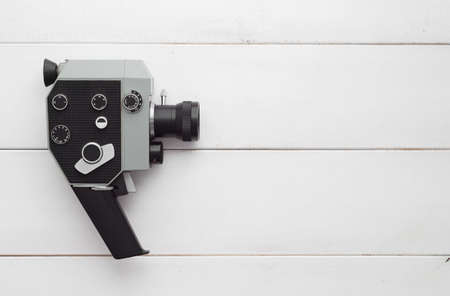Vintage video camera over white wooden table, above view and with copy space for text or other desing Banco de Imagens