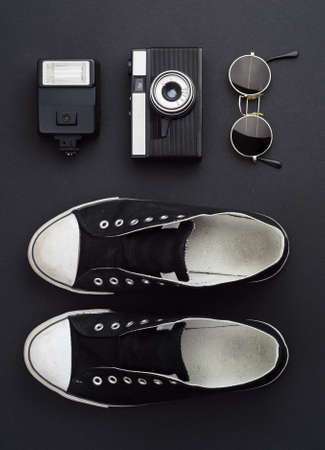 trip over: Concept: Ready for a trip. Sneakers, photo camera, flash, and round sunglasses well organized over black background. All the objects are black