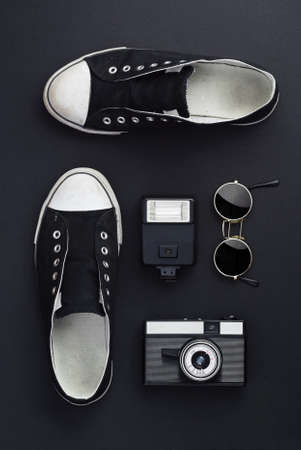trip over: Concept: Ready for a trip. Sneakers, photo camera, and round sunglasses well organized over black background. All the objects are black