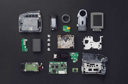 deconstruct: Parts of a mini DV video camera separate and well arranged over black background, above view. Stock Photo