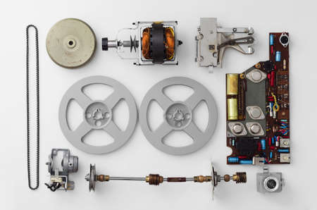 deconstruct: Parts of a vintage film projector well arranged over white background, above view. This is part of a larger series.