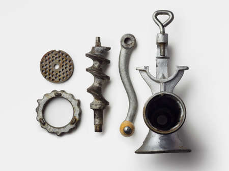 disassemble: Metal meat grinder well arranged over white background, above view