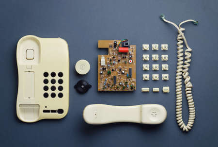 organized home: Parts of vintage home telephone well organized over dark blue background, above view. This image is part of a larger series. Stock Photo