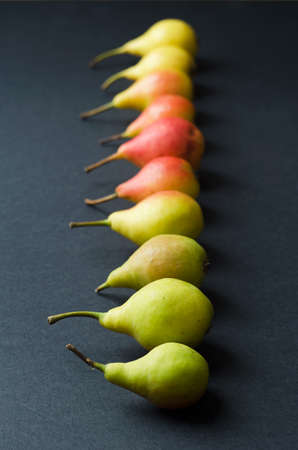 organized: Multiple colorful pears organized in a row over black background