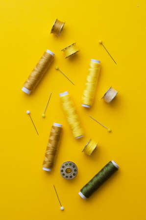 cotton thread: Colorful thread spools over bright yellow background, above view Stock Photo