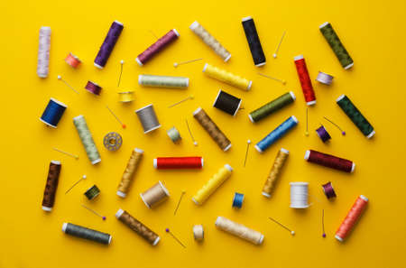 Colorful thread spools disorganized over bright yellow background, above view