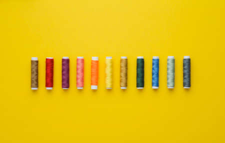 yellow  green: Colorful thread spools in a row over bright yellow background, above view Stock Photo