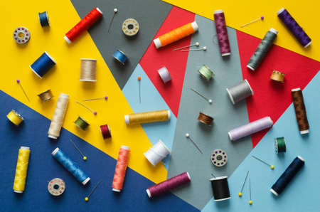 disorganized: Colorful thread spools disorganized over bright colorful background, above view