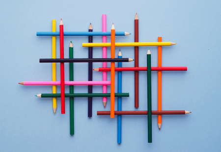neatly: Collection of colorful crayons over blue background, above view