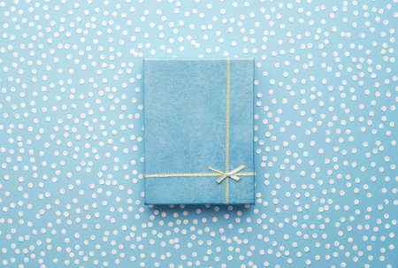 colour box: Christmas Gift Box with snow confetti over blue background, above view