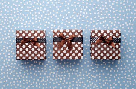 Cajas de regalo de Navidad con confeti de nieve en una fila sobre fondo azul, vista superior Foto de archivo - 44194720