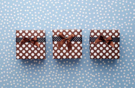 hilera: Christmas Gift Boxes with snow confetti in a row over blue background, above view Foto de archivo