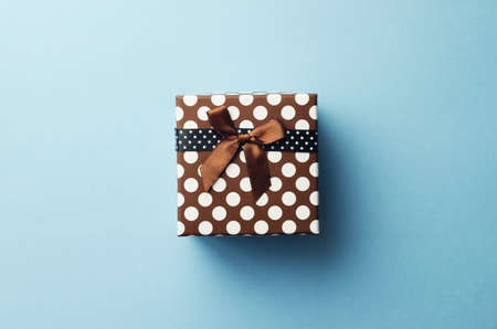 Christmas present box over blue background, above view.