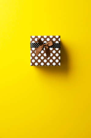 bright color: Christmas present box over bright yellow background, above view.