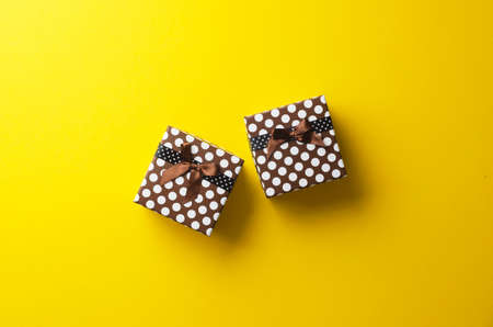 presents: Christmas present box over bright yellow background, above view.