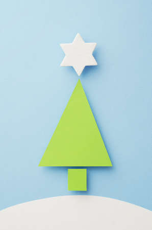 topper: Paper Christmas Tree and Star Tree Topper cut from green paper over blue background, top view