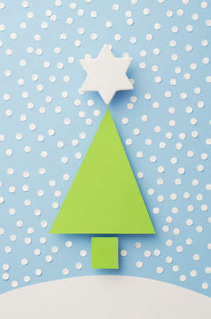 topper: Paper Christmas Tree, Star Tree Topper and snow cut from paper over blue background, top view Stock Photo