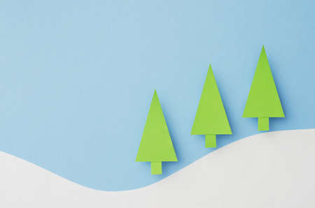small paper: Small Paper Christmas Trees cut from green paper over blue background Stock Photo