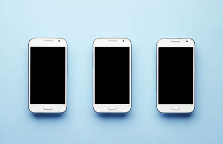 multiple: Three White Smart Phone over blue background, top view