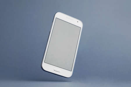 angle: White Smart Phone tilted in the air with shadow over dark blue gray background. Clipping path around the phone screen. Stock Photo