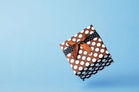 background colors: Gift box with dots floating in the air over blue background with copy space Stock Photo