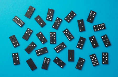 disorganized: Domino pieces disorganized over blue background, top view