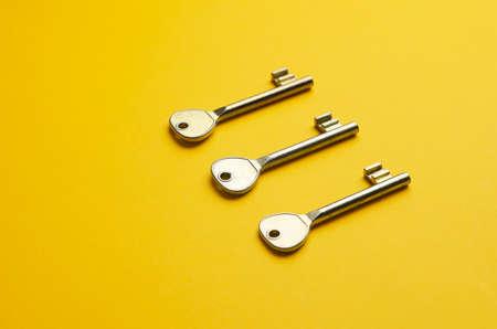 llaves: Llaves de la puerta simples organizadas en una disputa sobre fondo amarillo brillante Foto de archivo