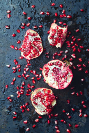 black metallic background: Pomegranates over dark black metallic background, above view