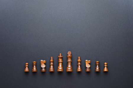 organized: Wooden chess figurines organized in a row over black background