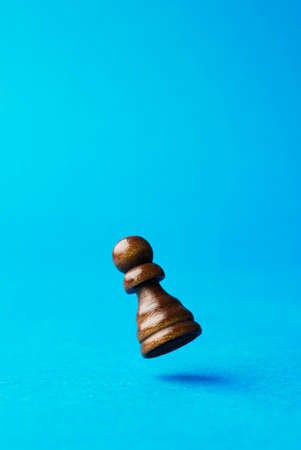 pion: The Pawn, wooden chess figurine falling on the ground Stock Photo