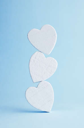 matrimonio feliz: Pila de corazones de madera sobre fondo azul