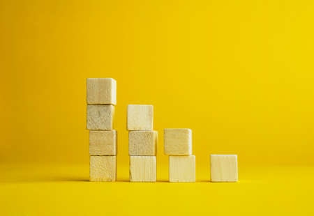 descending: Descending graphic made of wooden cubes over bright yellow background