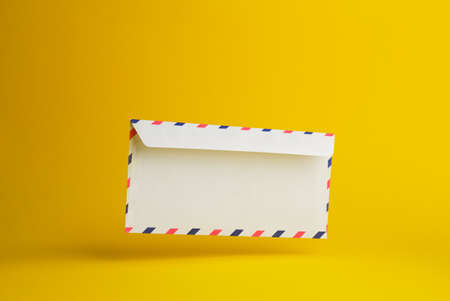 negative space: Envelope falling on the ground, yellow background with negative space